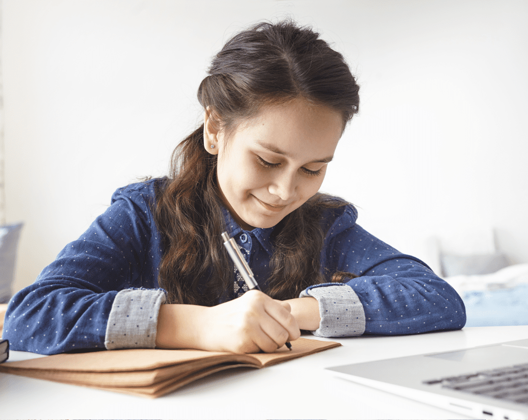 young teen taking notes during online class