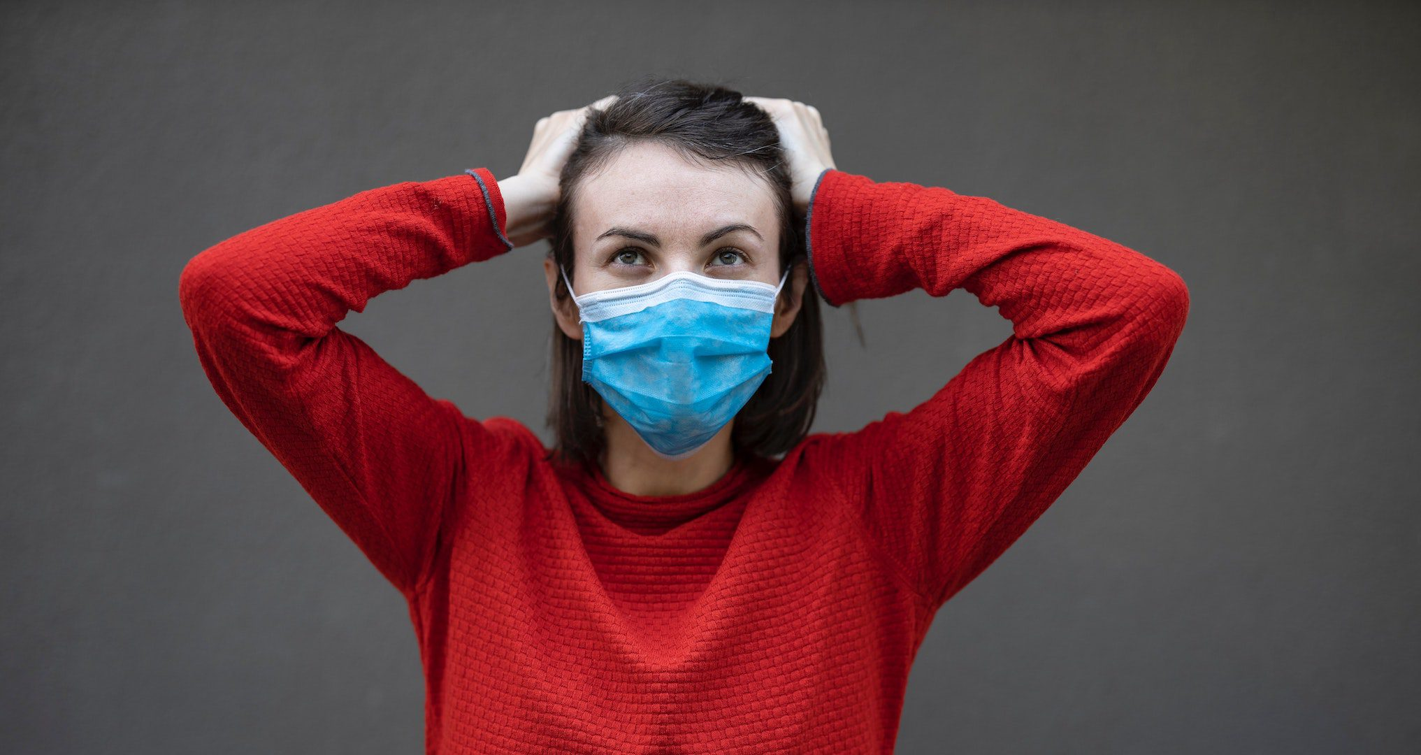 woman wearing a face mask and holding her head
